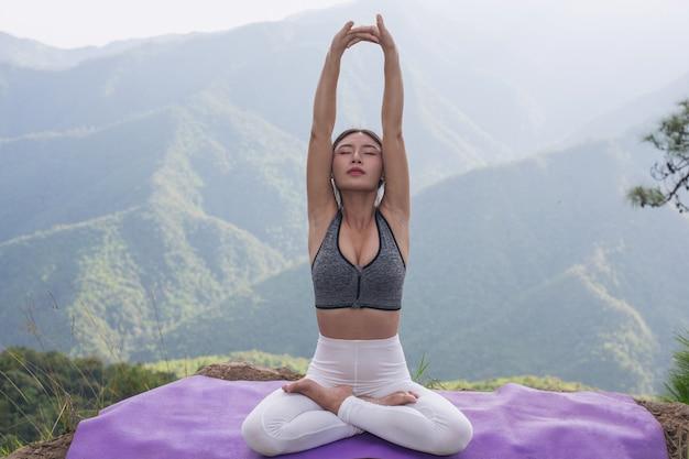Hermosa joven meditando y haciendo ejercicio encima de él.