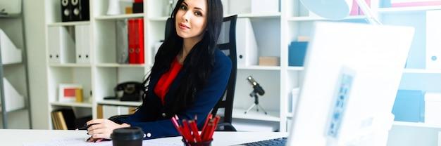 Hermosa joven está mirando a través de documentos, sentado en la oficina en la mesa.