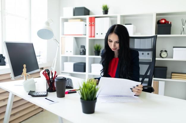 Hermosa joven está mirando a través de documentos, sentado en la oficina a la mesa