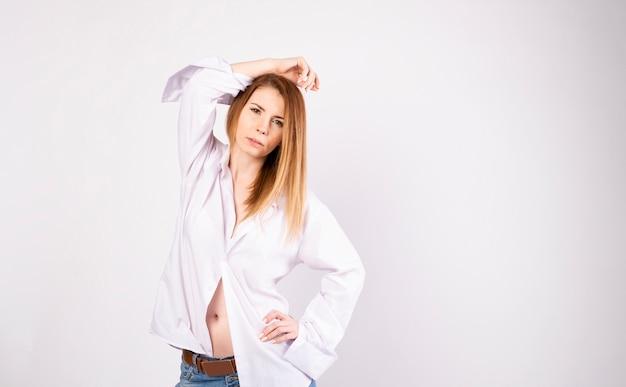 Hermosa joven modelo en camiseta blanca y jeans sobre fondo blanco.