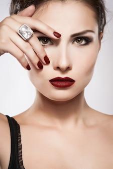 Hermosa joven modelo con labios rojos y manicura roja.