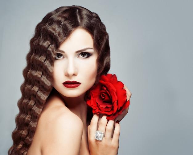 Hermosa joven modelo con labios rojos y rosa roja.