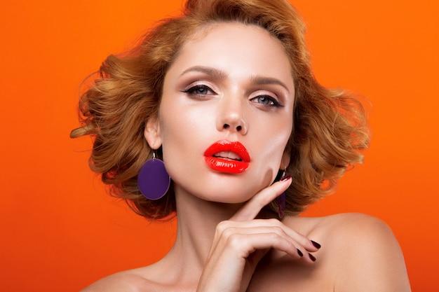 Hermosa joven modelo con labios rojos, sobre un fondo naranja