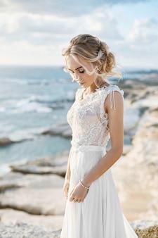 Hermosa joven modelo rubia mujer con maquillaje desnudo en un vestido de novia de moda caminando en la costa del mar en chipre