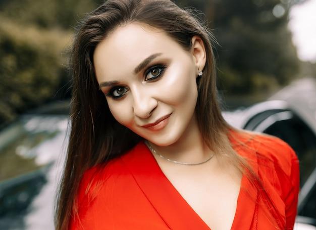 Una hermosa joven con un mono rojo se encuentra junto a un coche negro en una carretera vacía en el bosque