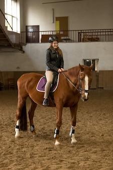 Hermosa joven montando a caballo marrón en interior manege