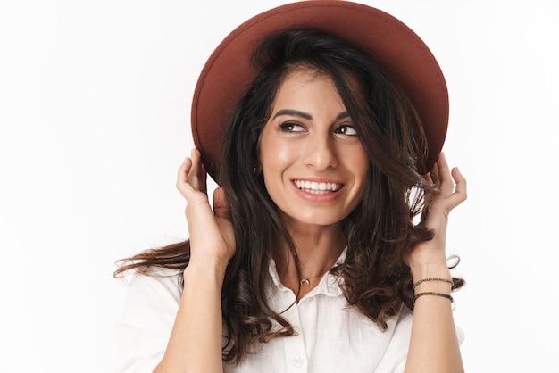 Hermosa joven morena alegre vistiendo ropa casual que se encuentran aisladas sobre la pared blanca, posando con un sombrero