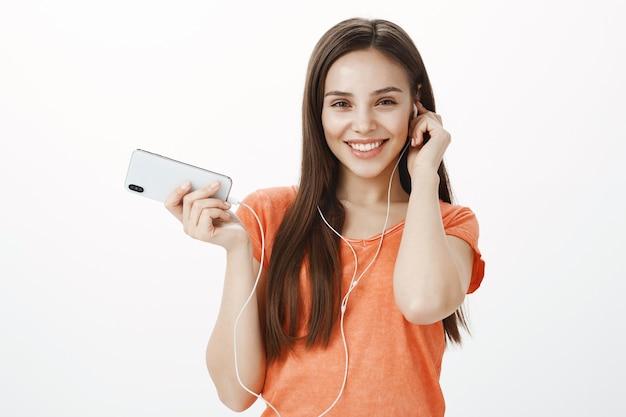 Hermosa joven morena escuchando música en auriculares y sosteniendo el teléfono móvil