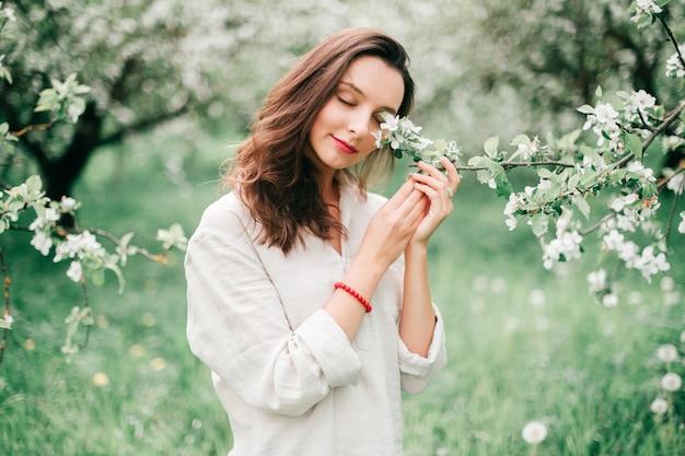 Hermosa joven morena con labios rojos posando en manzanos florecientes en bosque de la primavera.