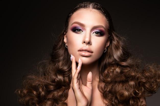 Hermosa joven morena con maquillaje y cabello rizado