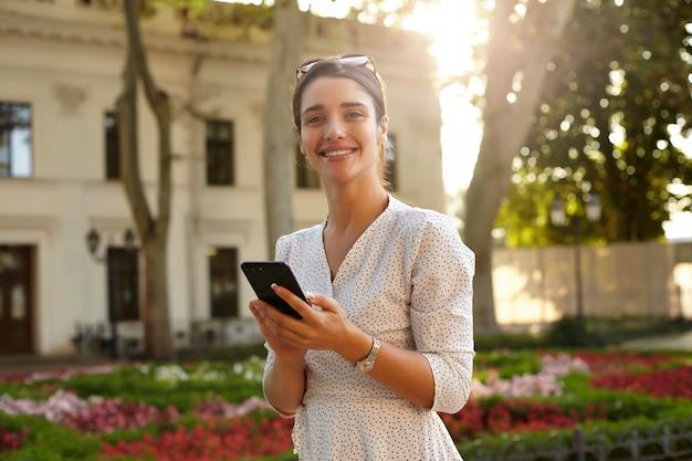 Hermosa joven morena de ojos marrones con teléfono móvil en sus manos mirando positivamente con una sonrisa encantadora, estando de buen humor mientras camina por la calle