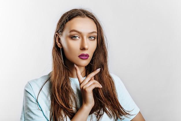 Hermosa joven morena de ojos verdes con cabello largo con maquillaje de moda con labios morados sobre un fondo gris aislado. la mujer se lleva la mano a la cara y mirando seriamente a la cámara.