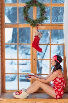 Hermosa joven morena con pijama rojo sentado en casa junto a la ventana