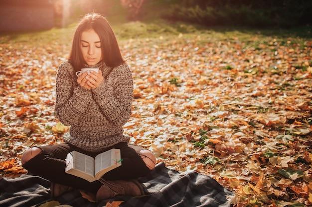 Hermosa joven morena está sentada en un otoño caído deja en un parque, modelo femenino está bebiendo té o café y leyendo un libro