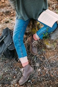 Hermosa joven morena sentarse bajo el árbol leer libro