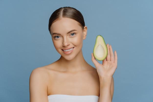 Hermosa joven morena tiene la mitad de aguacate disfruta de cosméticos orgánicos