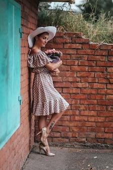 Hermosa joven morena en vestido begie dot posando al aire libre cerca de la pared de ladrillo rojo