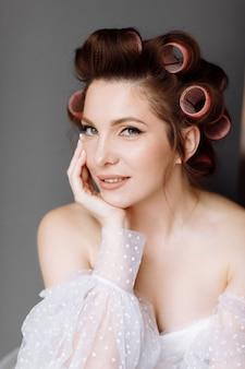 Una hermosa joven morena vistosa con maquillaje de pin-up brillante en un vestido largo de encaje blanco y rulos rosados. concepto de belleza.