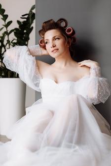 Una hermosa joven morena vistosa con maquillaje de pin-up brillante en un vestido largo de encaje blanco y rulos rosados.