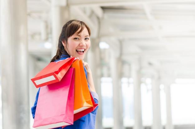 Hermosa joven mujer de asia con bolsas de compras.