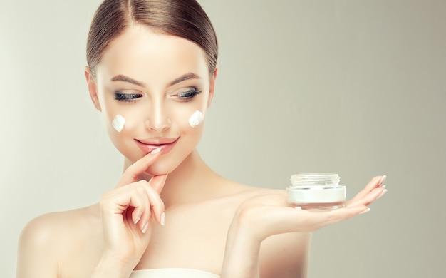Hermosa, joven, mujer de cabello castaño con manchas de crema cosmética en la piel bien arreglada