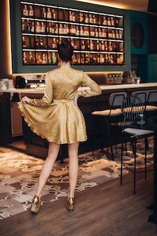 Hermosa joven mujer caucásica con cabello oscuro en vestido plateado y zapatos posa para la cámara y muestra su nuevo vestido