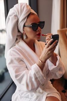 Hermosa joven mujer caucásica con cabello rubio en gafas de sol, vestido morado, vestido negro se sienta en su acogedora habitación y hacer maleup