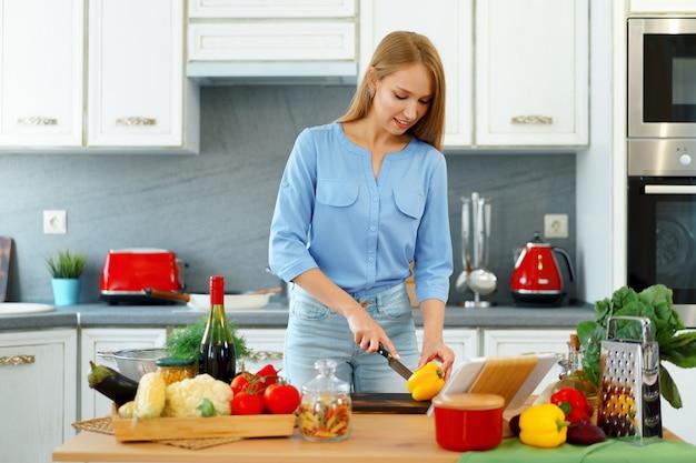 Hermosa joven mujer caucásica cocinar y usar su tableta digital en la cocina