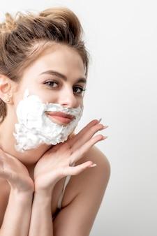 Hermosa joven mujer caucásica con espuma de afeitar en la cara posando en la pared blanca