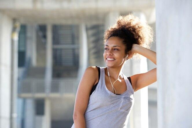 Hermosa joven mujer de deportes sonriendo con auriculares
