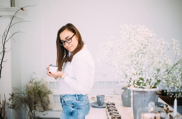Hermosa joven mujer femenina en elegantes gafas sonriendo con una taza de café, vestida con ropa casual de moda en una habitación luminosa con flores frescas