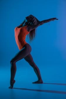 Hermosa y joven mujer gimnasta en forma con vestido azul de ropa deportiva trabajando, realizando un elemento de gimnasia artística, saltando, haciendo un salto dividido en el aire, bailando