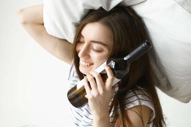 Hermosa joven mujer morena que tiene resaca sosteniendo una almohada blanca sobre su cabeza y una botella de alcohol en su mejilla