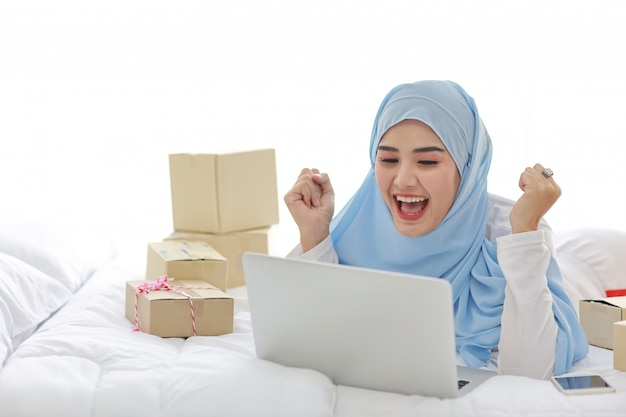 Hermosa y joven mujer musulmana asiática en ropa de dormir con aspecto atractivo, se encuentra en la cama con la computadora, teléfono móvil y entrega de caja de paquete en línea. la mujer inteligente con hijab recibe buenas noticias y sorpresas.