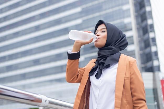 Hermosa joven musulmana asiática agua potable.