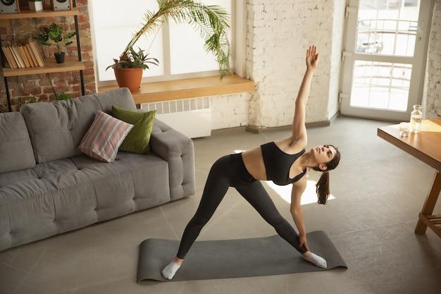 Hermosa joven musulmana tomando lecciones profesionales de yoga en línea y practicando en casa.