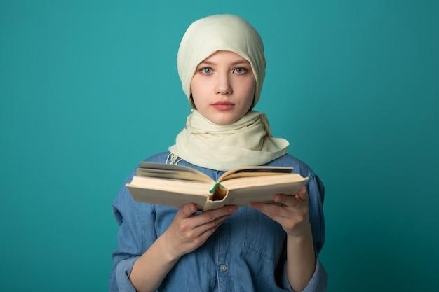 Hermosa joven musulmana en velo leyendo un libro