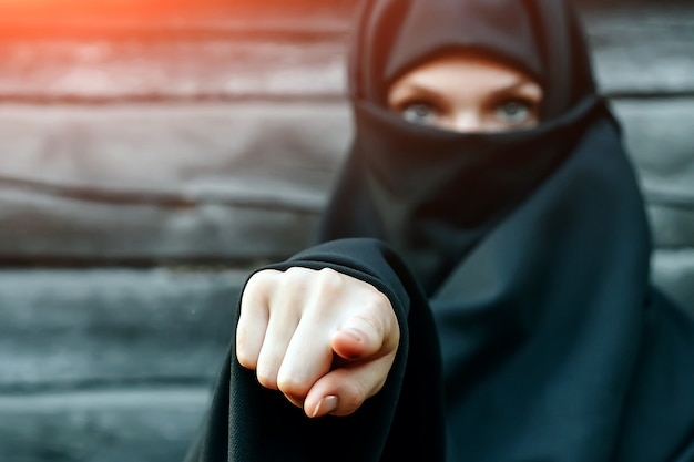 Una hermosa joven musulmana con un velo negro con la cara cerrada contra un árbol gris señala con el dedo a la cámara. copyspace