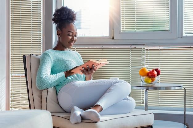 Hermosa joven negra leyendo libro cerca de la ventana en casa