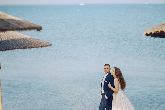 3244b7cc1 Hermosa joven novia de pelo largo en vestido blanco con su joven esposo en  la playa