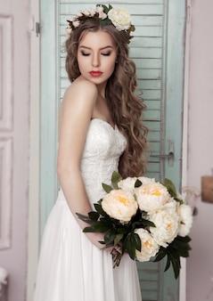 Hermosa joven novia con flores de corona y decoración romántica rosa y verde. cajas de madera botellas y diferentes decoraciones de boda