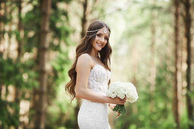 Hermosa joven novia con peinado de novia con joyas en vestido de encaje con un ramo de flores en sus manos y posando en el bosque temprano en la mañana