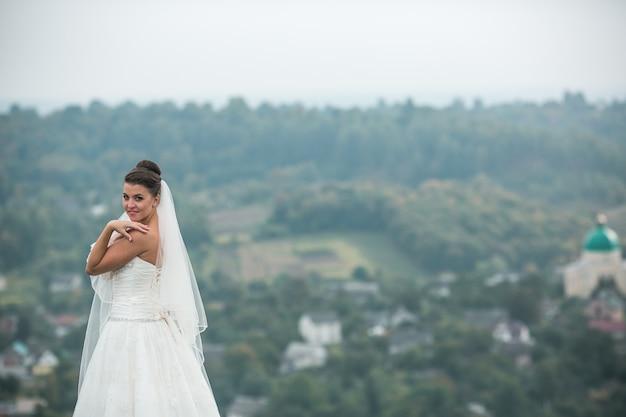 Hermosa joven novia posa para la cámara en el fondo de la ciudad en la distancia