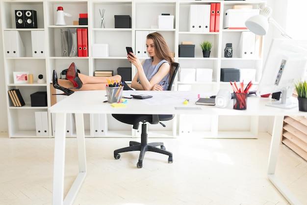 Una hermosa joven en la oficina ha puesto los pies sobre la mesa y sostiene gafas y un teléfono.