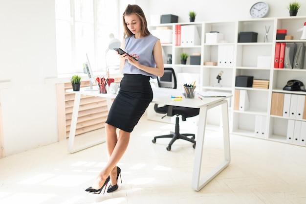 Hermosa joven en la oficina está de pie cerca de la mesa, con gafas en la mano y mirando la pantalla del teléfono.