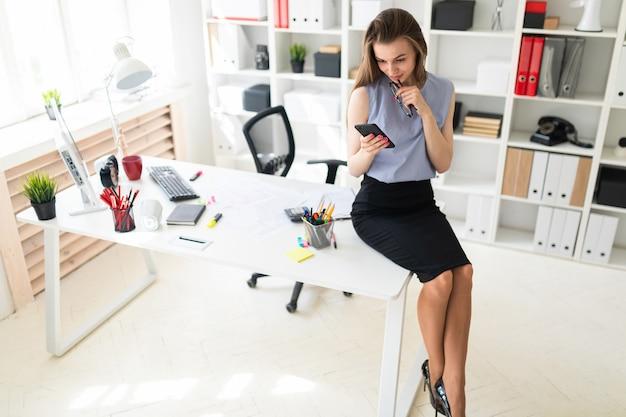 Hermosa joven en la oficina está sentado en el escritorio y sostiene gafas y un teléfono.