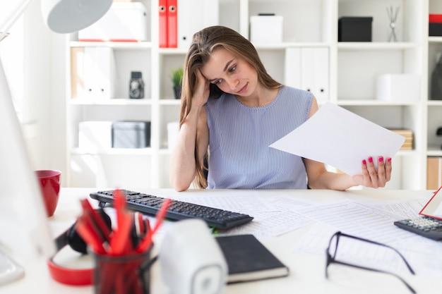 Hermosa joven en la oficina se sienta a la mesa y busca documentos.