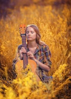 Hermosa joven con los ojos cerrados se sienta en un campo en una guitarra acústica