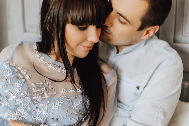 Hermosa joven pareja abraza tierna sentada en una cama