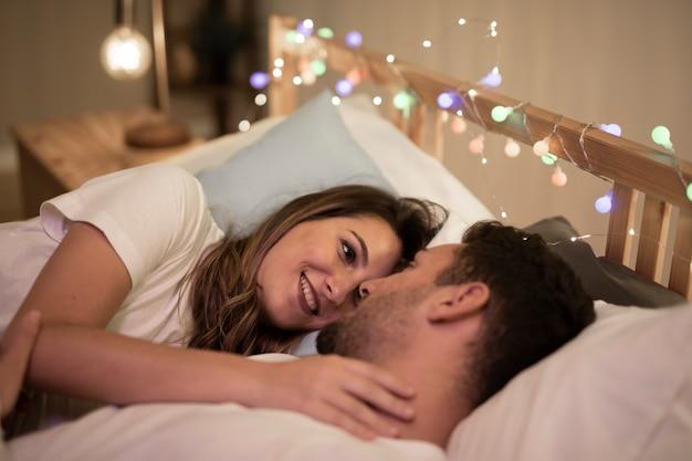 Hermosa joven pareja abrazados en la cama
